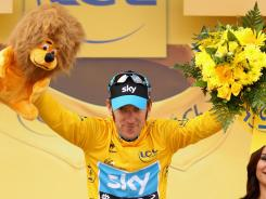 Bradley Wiggins of Great Britain celebrates on the podium after securing the yellow jersey of the general classification during Stage 19 of the 2012 Tour de France.