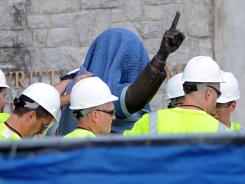 Workers remove the statue of former football coach Joe Paterno outside Beaver Stadium on Penn State's campus in State College, Pa.