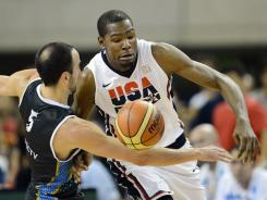 USA guard Kevin Durant (right) battles for a loose ball with Argentina's Manu Ginobili during the first half of an exhibition game Sunday in preparation for the London Olympics.