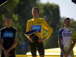 Great Britain's Bradley Wiggins, center, poses with second-placed Christopher Froome, left, and third-placed Vincenzo Nibali, right, on the podium at the end of the 2012 Tour de France.