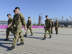 Security forces patrol with Olympic Stadium and the Orbit Tower in the background before the Games.