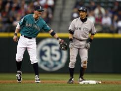 New York Yankees outfielder Ichiro Suzuki is greeted by Seattle Mariners shortstop Brendan Ryan following a stolen base during the third inning at Safeco Field.