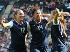 USA forward Lauren Cheney (12) celebrates with forward Abby Wambach (14) and forward Alex Morgan (13) after scoring on France during the women's preliminary match before the London Olympics.