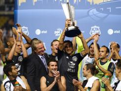 D.C. United midfielder Dwayne De Rosario holds up the trophy after the MLS All-Stars defeated the reigning European champion Chelsea.