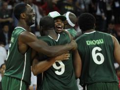 Nigeria players, including Chamberlain Oguchi (9) and Ike Diogu (6), celebrate after upsetting Greece during the quarterfinals of the FIBA Olympic Qualifying Tournament on July 6.