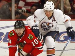 Defenseman Steve Staios, right, checks Patrick Sharp during a March 2008 game.