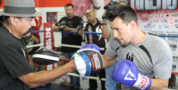 Robert Guerrero works the mitts with his father, Ruben Guerrero, left, during a media workout this week.