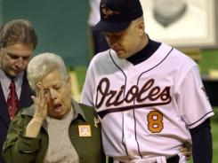 Cal Ripken escorting his mother, Vi, from the field, after throwing out the ceremonial first pitch before Cal's final game in 2001.