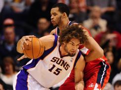 Center Robin Lopez, left, driving to the basket against Wizards center JaVale McGee during a Feb. 20 game, will play alongside 6-11 forward Anthony Davis for the Hornets this season.