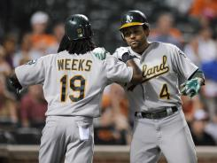 Athletics' Coco Crisp celebrates with Jemile Weeks after they both scored on a double by Seth Smith during a six-run ninth inning against the Baltimore Orioles.