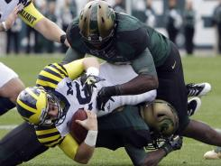 Michigan State linebacker Chris Norman, top, will lead a strong Spartans defense this season