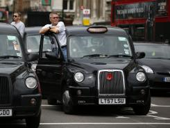 London taxi drivers park their cabs on the junction of Whitehall and Parliament Square, as they take part in a protest to jam traffic in reaction to not being allowed to use the Olympic driving lanes in London on July 17.