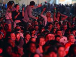 Spectators dance in the crowd while watching the Olympics Opening Ceremony on a big screen at Victoria Park in London.