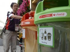 Bins are placed around Olympic Park to help with recycling in an effort to promote green Games. Here Anna Kent, a nurse at the Games from Nottingham, uses the bins outside the Main Press Center.