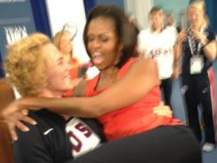 First lady Michelle Obama gets a lift from U.S. wrestler Elena Pirozhkova.