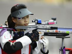 Top-ranked Yi Siling of China captures the first gold medal of the London Games with a victory in the women's 10-meter air rifle competition at Royal Artillery Barracks.