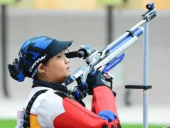 Nur Suryani Mohamed Taibi of Malaysia adjusts her rifle during the women's 10-meter air rifle qualification round at the Royal Artillery Barracks on Saturday.