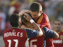 Real Salt Lake's Javier Morales and Will Johnson, right, congratulate Alvaro Saborio on his goal on a penalty kick against the Vancouver Whitecaps.