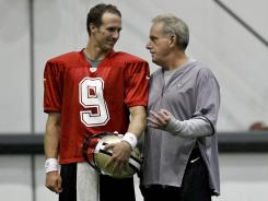 Saints quarterback Drew Brees talks with interim head coach Joe Vitt during the first day of of training camp at the team's indoor practice facility.