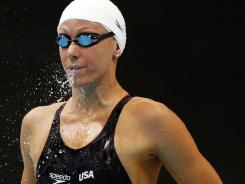 Dana Vollmer spits out a mouthful of water before competing in a women's 100-meter butterfly heat Saturday at the London Olympics.