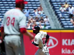 Braves' Jason Heyward, right, rounds the bases after hitting a first inning home run against Phillies' Roy Halladay.