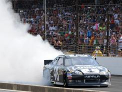 Jimmie Johnson smokes his tires on the frontstretch at Indianapolis Motor Speedway to celebrate his fourth Brickyard 400 win.
