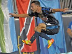 Union forward Jack McInerney jumps over the dasher board on his way to celebrate with fans after scoring the game winning goal against the Revolution.