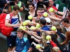 Andy Murray of Britain signs autographs for fans after his first-round victory against Stanlisas Wawrinka in Olympic men's singles.