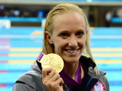 U.S. swimmer Dana Vollmer poses with her gold medal after winning the women's 100 butterfly final with a world-record time Sunday.