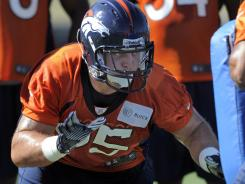 Broncos rookie defensive tackle Derek Wolfe runs a drill during the opening session of training camp in Englewood, Colo.