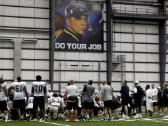 Persistent presence: A sign featuring suspended head coach Sean Payton hangs overhead Friday as Saints players huddle on the field after practice at the team's indoor facility in Metairie, La. The sign was owner Tom Benson's idea.