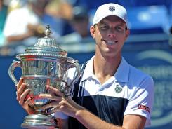 Sam Querrey poses with the trophy after defeating Ricardas Berankis 6-0, 6-2 for his third Farmers Classic championship.