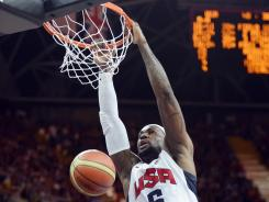 Take that: U.S. forward LeBron James dunks over French center Ali Traore on Sunday.