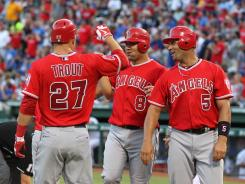 Angels designated hitter Kendrys Morales, center, celebrates his sixth inning grand slam with Albert Pujols and Mike Trout.