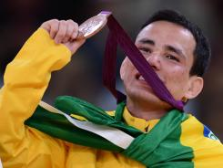 Brazil's Felipe Kitadai poses with his bronze medal on the podium after the men's 60-kilogram judo competition.