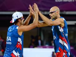 Todd Rogers, left, and Phil Dalhausser of the USA celebrate after their opening-round beach volleyball victory Sunday.