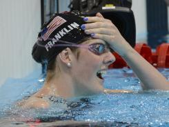 Missy Franklin checks the results board, confirming that she had won the 100 backstroke.
