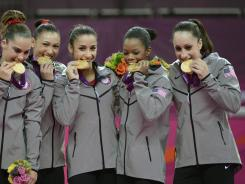 USA gymnasts McKayla Maroney, Kyla Ross, Alexandra Raisman, Gabrielle Douglas, Jordyn Weiber celebrate with their gold medal after the women's team gymnastics final during the London 2012 Olympic Games at North Greenwich Arena.