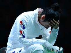 South Korean fencer Shin A-lam sits dejectedly after officials announce the results of the technical issue with the timing in her semifinal against Germany's Britta Heidemann in the women's epee competition.