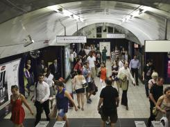 Travelers pass through a busy Tube station in London.