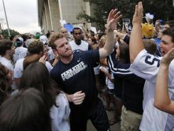 Penn State University quarterback Matt McGloin, center left, and his teammates are greeted by a pep rally of supporters on the way to a morning workout outside the Lasch Football building.