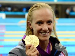 The USA's Dana Vollmer poses with her gold medal after winning the women's 100-meter butterfly with a world-record time of 55.98 seconds.
