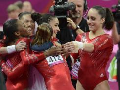 Jordyn Weiber, right, and her teammates hug after the vault competition in the women's gymnastics team final.