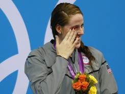 Missy Franklin reacts on the podium after receiving her gold medal for winning the women's 100-meter backstroke final during the London 2012 Olympic Games.