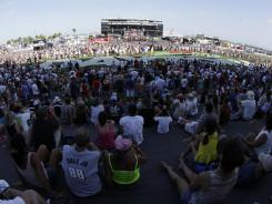 Fans listen to a concert by musical group Train prior to the Coke Zero 400 at Daytona International Speedway. Tracks are using more entertainment options to try to draw more people to their NASCAR races.