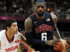 USA forward LeBron James drives past Tunisia forward Mohamed Hadidane during their game Tuesday. The U.S. team won its second Olympic game in a rout.