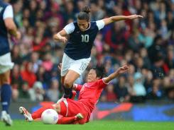 Carli Lloyd battles for the ball against North Korea forward Song Hui Kim.