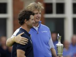 Adam Scott, left, is consoled by Ernie Els after losing the British Open to him by one shot July 22 after a collapse over the last four holes.