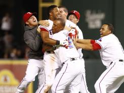 Rangers shortstop Elvis Andrus (1) gets swarmed by teammates after hitting a two-run walk-off single against the Angels on Wednesday night.