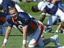 Denver quarterback Peyton Manning, warming up before the start of practice at the Broncos training facility, has created a vastly different atmosphere compared to last season's camp with Tim Tebow.
